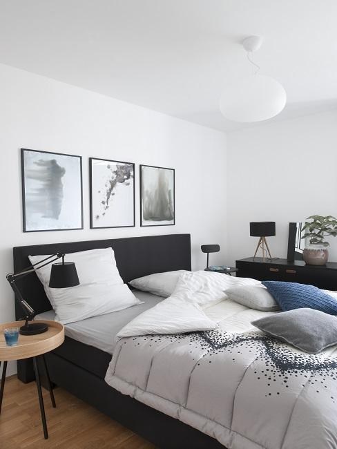 Biała sypialnia z łożkiem o ciemnej ramie, komodą oraz obrazami na ścianie