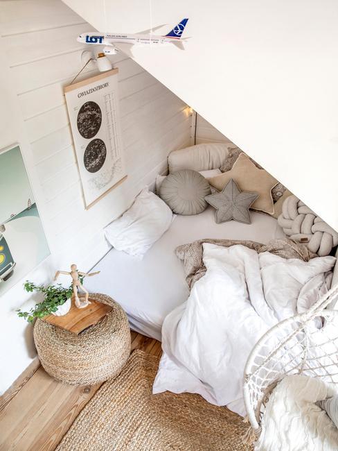 Łożko pod skosem w sypialni na poddaszu obok którego stoi puf