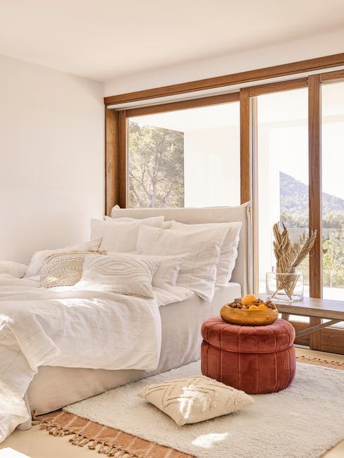 Biała sypialnia z dużym łożkiem ustawionym przy oknie i czerwony puf
