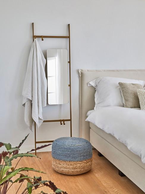 Biała sypialnia z łożkiem, jutowym pufem w kolorze niebieskim oraz rośliną