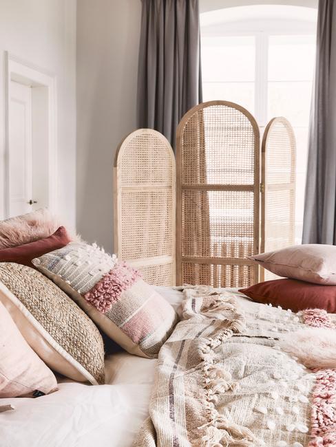 Zbliżenie na łożko z poduszkami oraz parawan w sypialnia boho