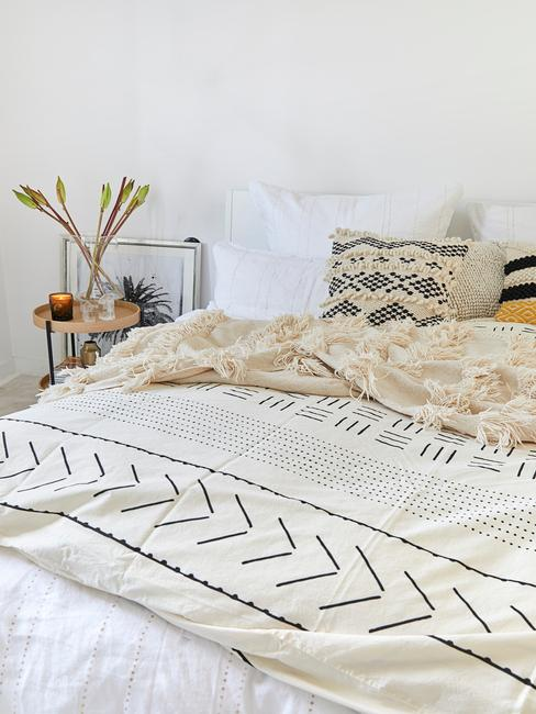 Zbliżenie na łożko przyktyre ocem w etno wzory i poduszki oraz stoliczek nocny
