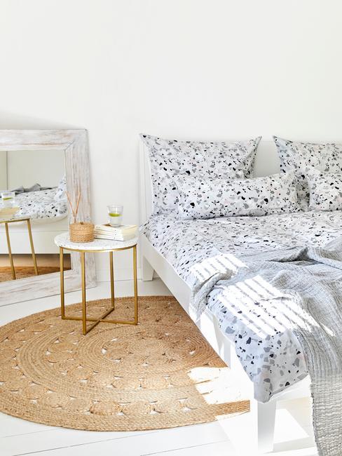 Sypialnia z łożkiem z niebiesko - białą pościelą, jutowym, okrągłym dywanem oraz stoliczkiem