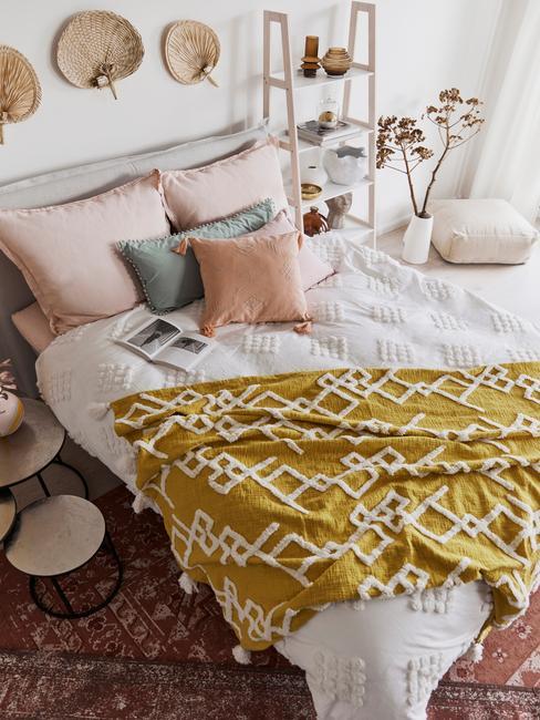 Zbliżenie na łóżko z żółtym kocem, kolorowymi poduszkami oraz słomkowym wachlarzami na ścianie