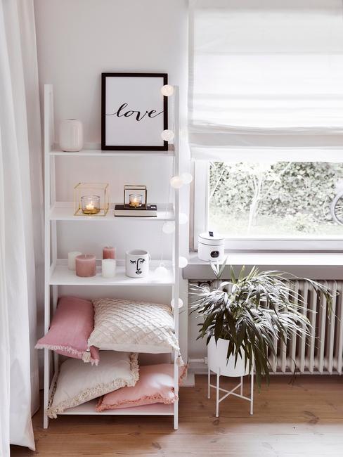 Zbliżenie na białą półkę z girlandą świetlną, biało - różowymi poduszkami, świeczkami i innymi dekoracjami