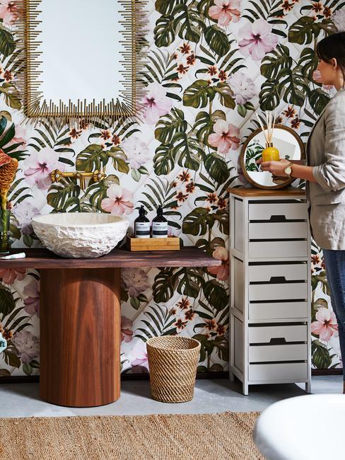 Łazienka z tapetą z roślinnym motywem, drewnianym blatem oraz białą szafką na chemię i kosmetyki