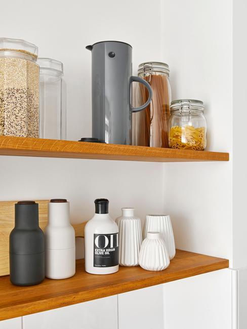 Zbliżenie na drewniane półki z przyprawami i białymi wazonami