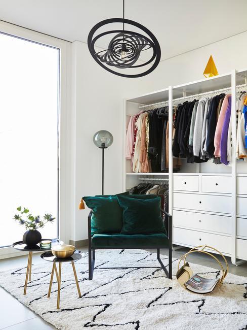 Zielony fotel z aksamitu, czarno-biały dywan, dwa stoliczki oraz biała szafa z ubraniami w garderobie
