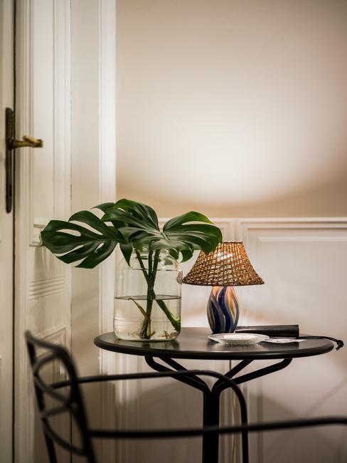 Stoliki z wazonem z liśćmi monstery i lampka w przedpokoju Autor Rooms