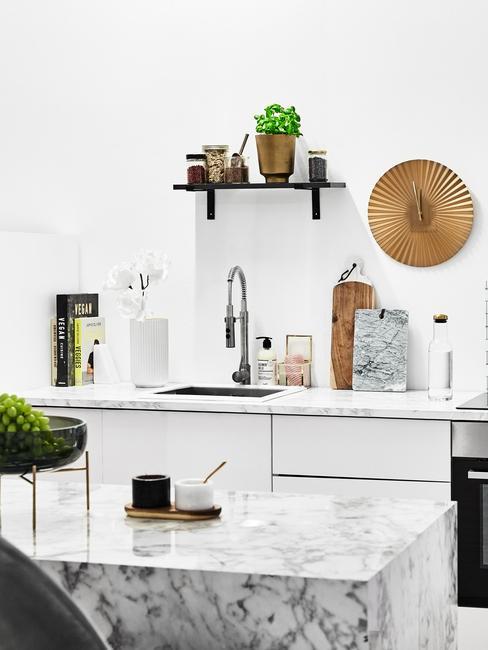 Biała kuchnia z marmurową wypsą, białymi meblami oraz akcesoriami kuchennymi