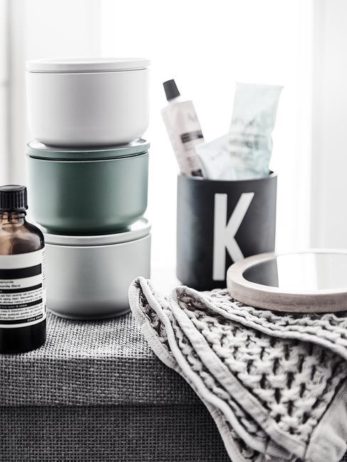 Kolorowe pojemniki do organizacji, czarny kubek oraz szary ręcznik na parapecie w łazience
