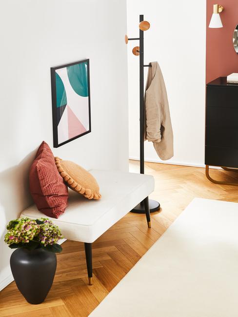 Przedposkój z białą ławką, dwoma poduszkami, rośliną w waznie i wieszakiem na ubrania