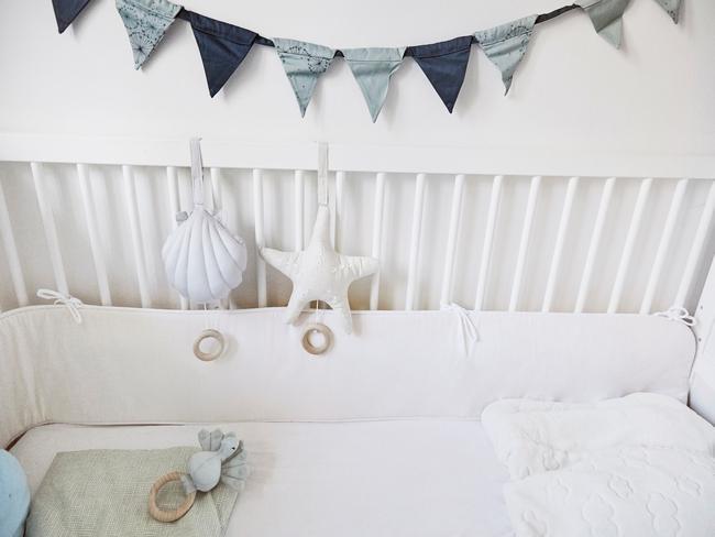 Zbliżenie na białe łóżeczko dziecięce z niebieską girlandą z chorągiewek