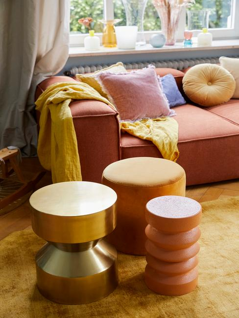 Wnętrze salonu z sofą Lennon z pomarańczowym ocieniu, pufy i żółty dywan