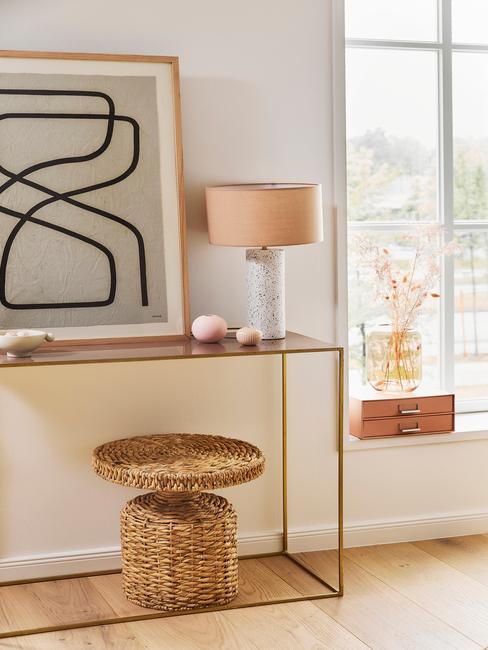 Zbliżenie na fragment pomieszczenia ze stołem, rattanowym stoliczkiem oraz obrazem