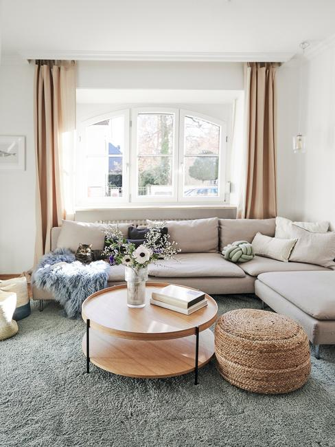 Wnętrze beżowego salonu z sofą, stolikiem oraz dywanem