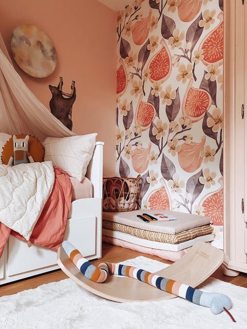 Różowy pokój dziecięcy z tapeta w figi na jednej ścianie, łożkiem oraz zabawkami