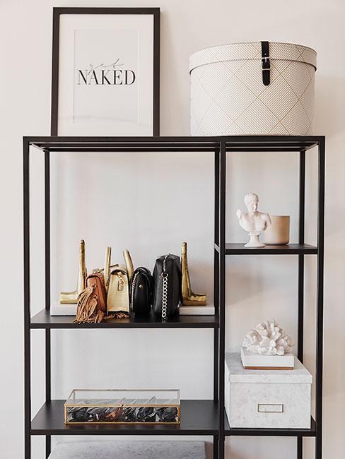 Czarny regał z wyeksponowanymi małymi torebkami i innymi dekoracjami z garderoby