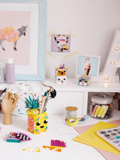 Zbliżenie na biurko z pokoju dziecięcym z akcesoriami i obrazkami na ścianie