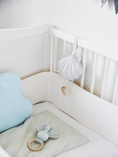 Zbliżenie na białe łóżeczko dziecięce z niebieską poduszką oraz zabawkami