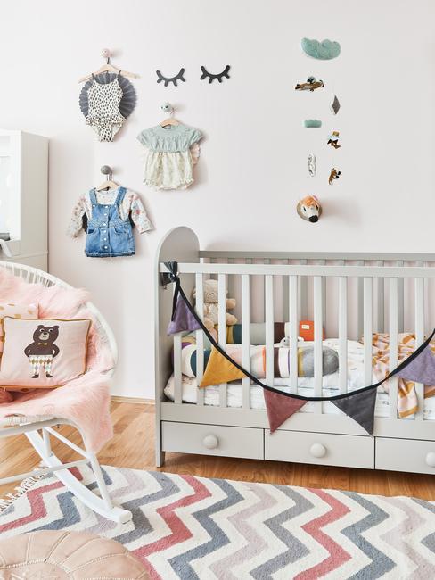 Pokój dziecka z drewnianym, białym łóżeczkem, krzesłem z kocem oraz wieszakami