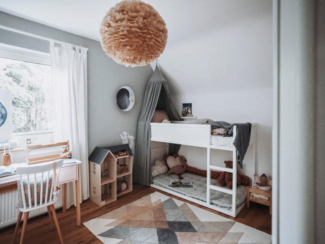 Pokój dziecięcy z łóżkiem piętrowym, dywanem, białym biurkiem oraz krzesłem