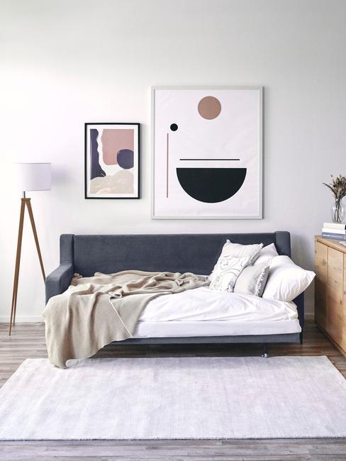 Rozkładana, ciemnoniebieska sofa z białą pościelą oraz obrazkami