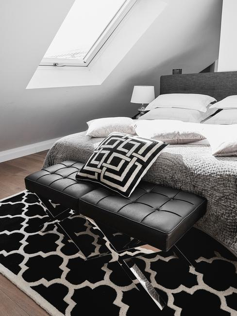 Sypialnia na poddaszu z czarnym dywanem, ławką oraz szarym łóżkiem