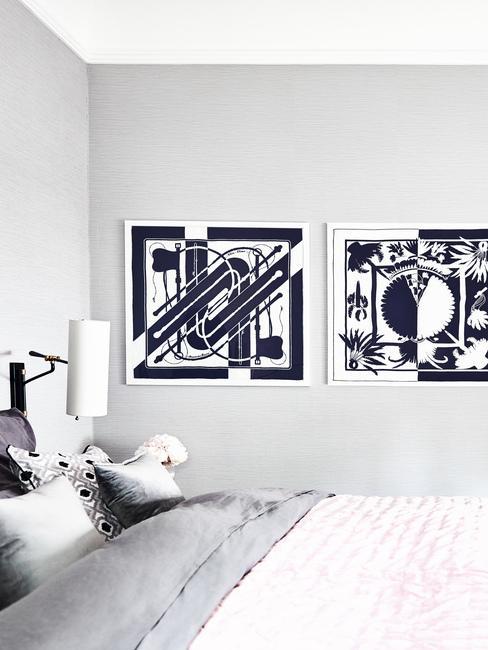 Biała sypialnia z łóżkiem, lampką oraz dwoma obrazami