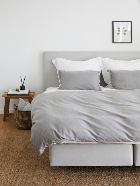 Biała sypialnia ze stoliczkiem nocnym, jutowym dywanem oraz łóżkiem z szarą pościelą