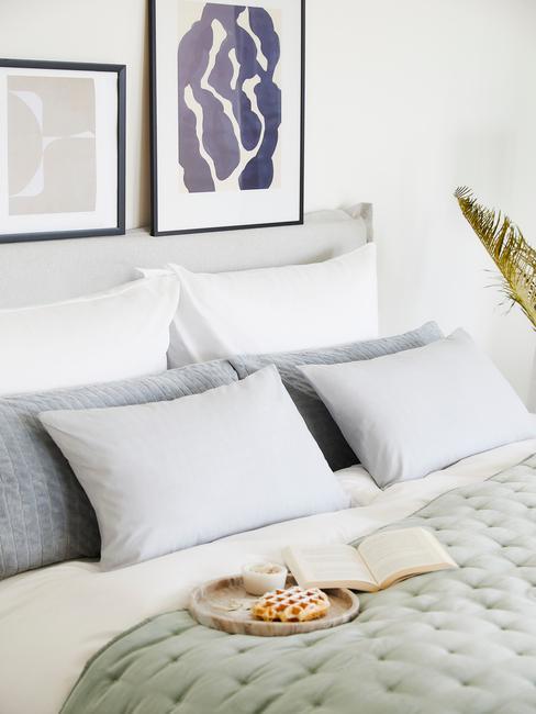 Zbliżenie na łożko w sypialni z jasnozieloną narzutą, poduszkami oraz tacą ze śniadaniem