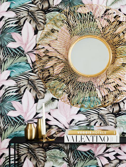 ściana z tapetą w kwiatowe wzory, złowe lustro oraz czarna półka z książkami i złotymi wazonami