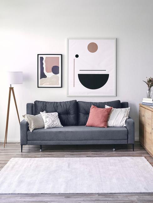 Wnętrze salonu w stylu skandynawskim z ciemnoniebieską sofą, poduszkami oraz obrazem
