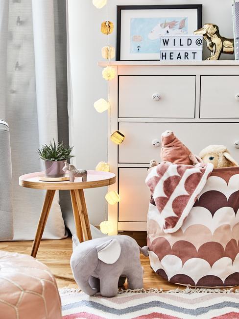 Biała komoda z lampkami cotton balls, zabawki oraz drewniany stoliczek