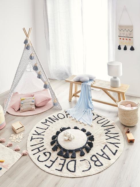 Kącik zabaw w białym pokoju z namiotem tipi, poduszkami i zabawkami
