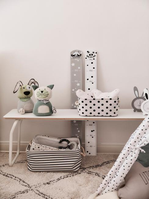 Fragment pokoju dziecięcego z białym stolikiem, zabawkami, miarkami wzrostu i fragmentem namiotu