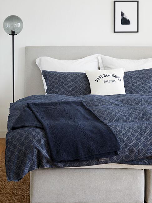 Łóżko z granatową narzutą