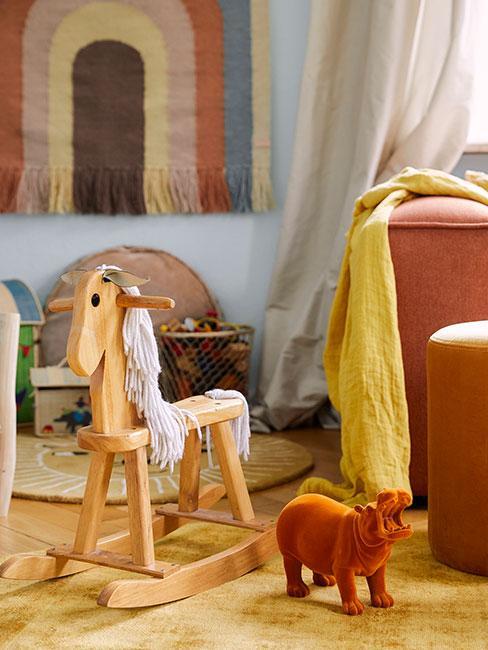 Drewniany konik na biegunach w salonie w ciepłych kolorach