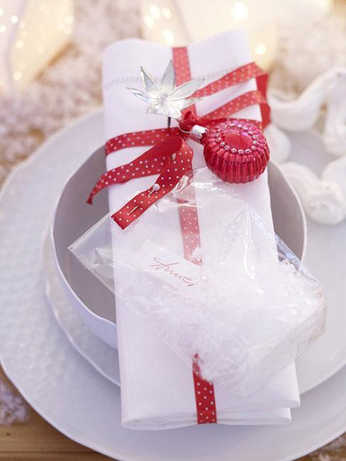 Biała serwetka przyozdobiona czerwoną wstążką  i bombką