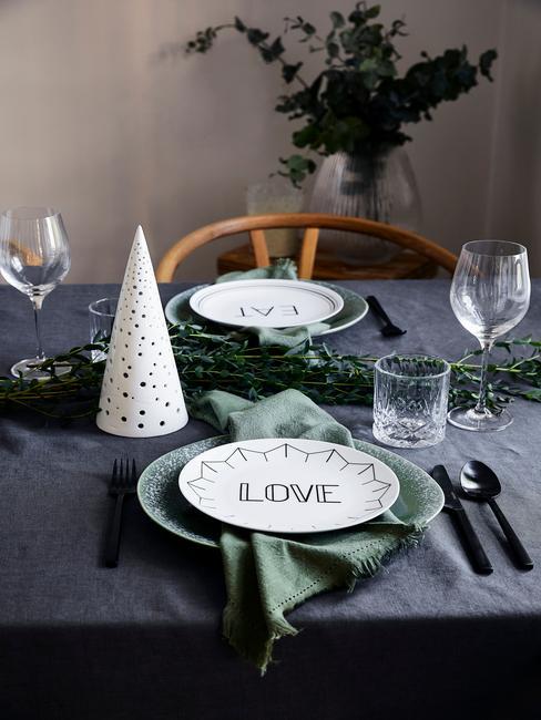 Stół z ciemnozielonym obrusem, zieloną zastawą, gałązką świerkową oraz białą dekoracją