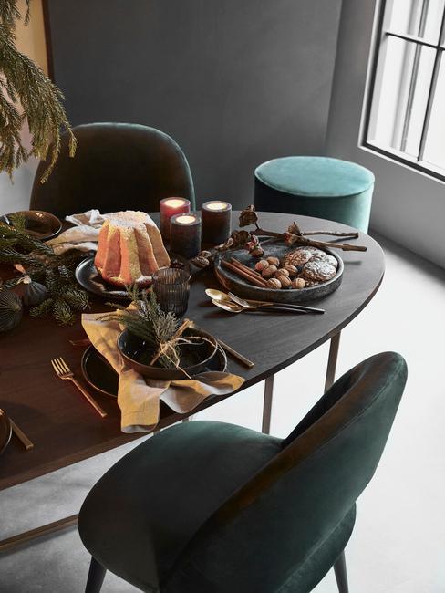 Fragment jadani z ciemnym, drewnianym stołem, zielonymkrzesłem oraz czarną zastawa