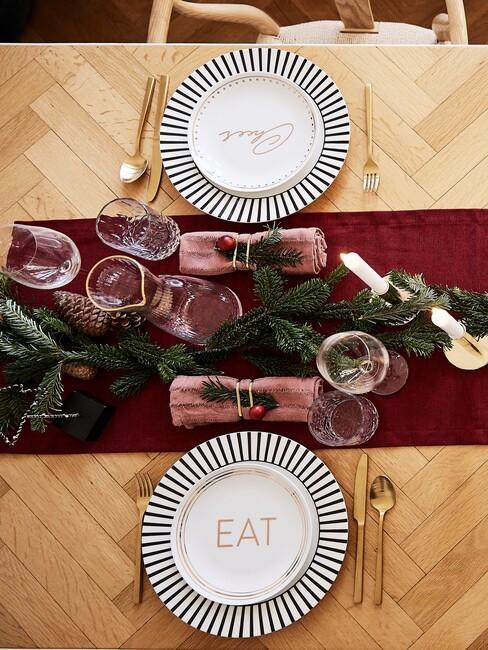 Dekoracja stołu wigilijnego z czerwonym bieżnikiem, białą zastawą oraz gałązkami świerku