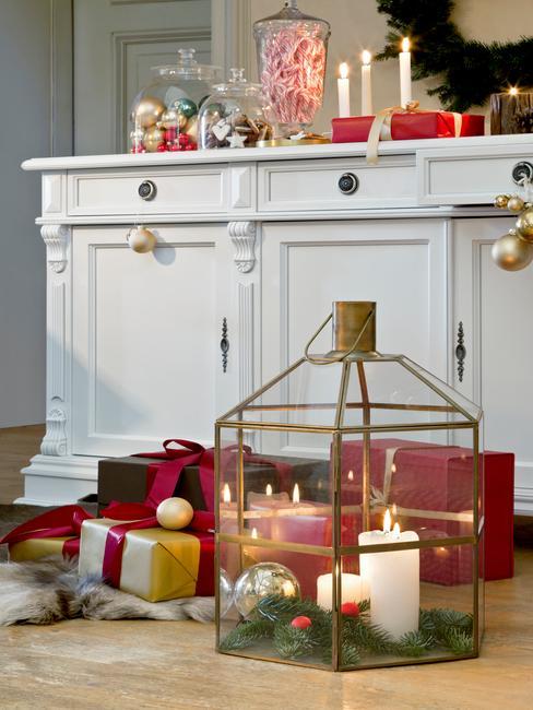 Biała komodaw przedpokoju ze świeczkami i dekoracjami oraz szklana latarenka na podłodze
