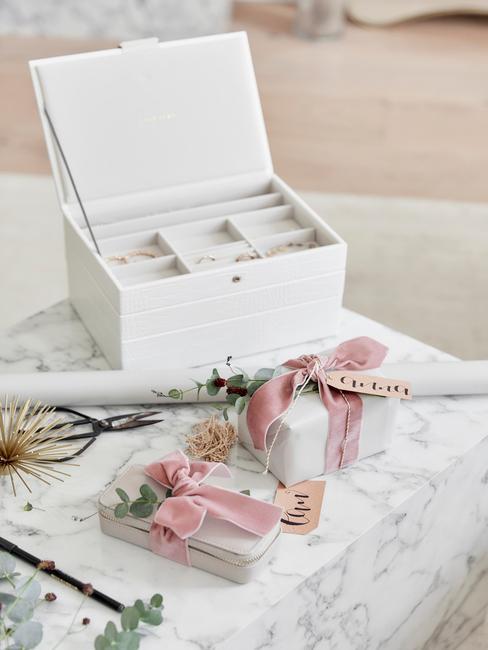 Białe pudełko na biżuterię ustawione na marmurowym stoliku kawowym z prezentami odwiniętymi różową wstażką