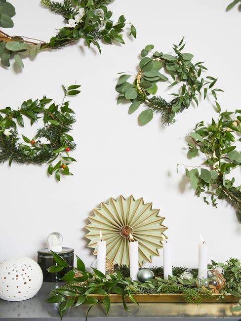 Przystrojona biała ściana za pomocą wieńców z eukaliptusa i świerku nad komodą ze śweczkami
