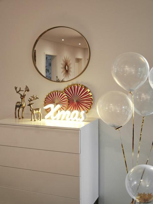 Biała komoda z dekoracjami świątecznymi, neonowym światłem nad którą wisi lustro