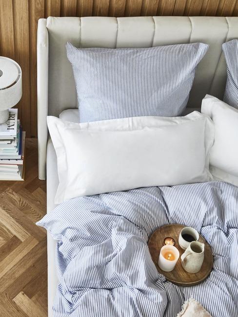 Łóżko z niebieską pościelą, białą poduszką i tacą z kubkami
