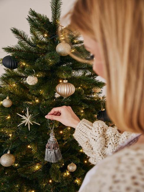 Kobieta dekorująca choinkę za pomoca złotych dekoracji