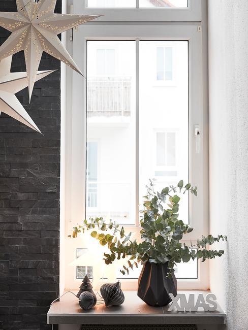 Świąteczna dekoracja okna lampkami, wazonem z bukietem eukaliptusa i bombkami