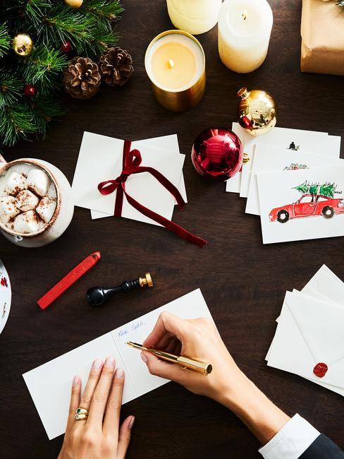 dłonie kobiece wypisujące kartkę na ciemnym stole z dekoracjami świątecznymi